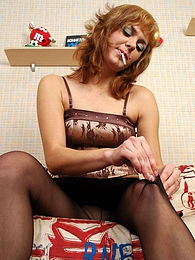 Smoking hottie fits black sheer-to-waist pantyhose on her long shapely legs pictures at freekilomovies.com