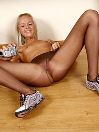Blond girl spreads her long legs in dark pantyhose filming her nyloned slit pics