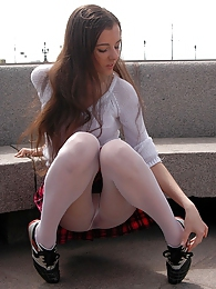 Innocent looking chick in smooth white pantyhose flashing upskirt outdoors pictures at adspics.com