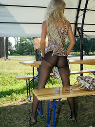 Long-haired blondie giving a glimpse of her slender legs in black pantyhose pictures at lingerie-mania.com