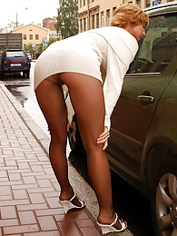 Naughty gal bending down and squatting flashing nyloned pussy in the street pictures at kilogirls.com