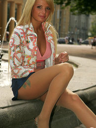 Sitting by the fountain blonde giving a glimpse of her pantyhose clad pussy pictures at freekilosex.com