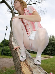 Brazen girl climbing a tree in her sheer white hose revealing her pink slit pictures at find-best-panties.com