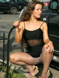 Pretty babe in shiny grey hose posing in the sun upskirt flashing in public pictures at freekilomovies.com