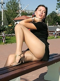 Sexy babe clad in pantyhose with extra sheen making upskirt show outdoors pictures