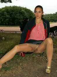 Upskirt babe clad in glossy tights making sexy spreads posing on the grass pictures at kilopics.net