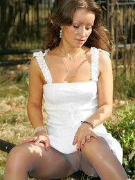 Beauty in light summer dress flashing outdoors in her glossy grey pantyhose pictures