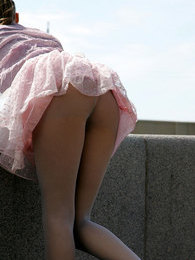 Bold girl posing outdoors in flying skirt and no panties under matte tights pictures at freekilomovies.com