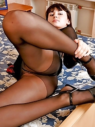 Curvy babe worshipping her slender legs in black pantyhose right in the bed pictures at freekiloclips.com