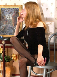 Lustful chick in nylon black pantyhose looking at a picture while smoking pictures at freekilomovies.com