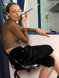 Seductive smoker in see-through top and silky pantyhose posturing topless pictures at lingerie-mania.com