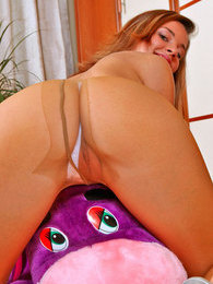 Naughty gal in flesh-colored pantyhose jumping on her favorite plush donkey pictures