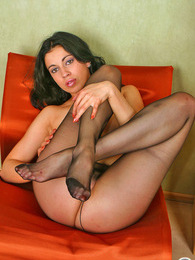 Playful brunette with tiny tits trying to stretch her silky black pantyhose pictures at freekilomovies.com