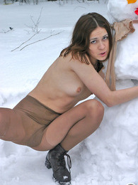Stunning chick in flesh-colored pantyhose making snowman in winter forest pictures