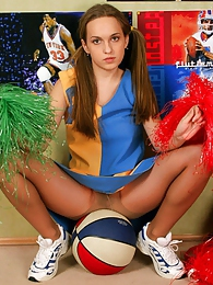 Lewd ponytailed cheerleader in flesh-colored pantyhose playing with a ball pictures at adspics.com