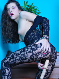 Dark-haired stunner stuffs her hairy pussy thru her black lacy bodystocking pictures at freekilosex.com