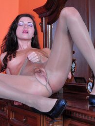 Slim-legged brunette in a little black dress and tan tights fucks her pussy pictures at freekilosex.com