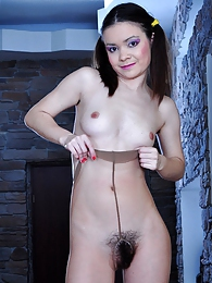 Ponytailed sweetie freaks out flashing her hairy pussy thru tan pantyhose pictures