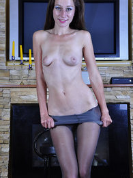 Leggy willowy girl showcases her v-top patterned pantyhose by the fireplace pictures