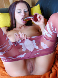 Heated girl dildo toying in her crimson pantyhose with a white flower print pictures at lingerie-mania.com