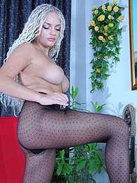 Busty long-haired blonde showing off her dotted black and white pantyhose pictures at freekilomovies.com