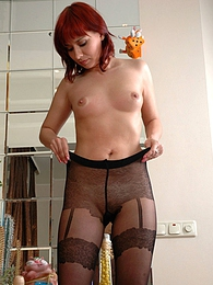 Cute redhead puts on her favorite tights with a gartered stockings effect pictures