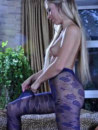Long-haired blonde admiring her shiny suntan and gorgeous blue fashion hose pictures at lingerie-mania.com
