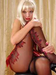 Tempting blonde hussy spreading legs in her sultry two-color fashion hose pictures