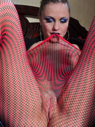 Passionate gal licks and stretches her stripy fishnets and fashion opaques pictures at lingerie-mania.com
