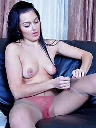 Horny brunette in tan pantyhose and a red thong plunging a huge rubber cock pictures at freekilosex.com