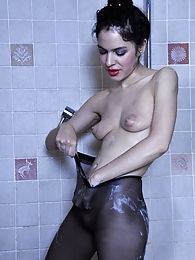 Kinky babe wets her black hose in the shower before changing out of them pictures at freekilosex.com