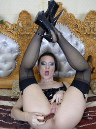 Corseted and stockinged brunette thrusts her shaved beaver on a glass toy pictures at kilovideos.com