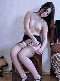 All-nude babe tries on a pair of sheer and black stockings with high heels pictures at freekiloclips.com