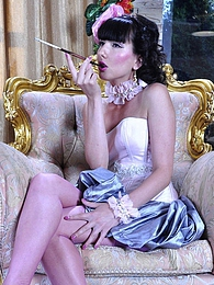 Glamour girl smokes a long cig and enjoys the feel of her pink shiny nylons pictures at freekilosex.com