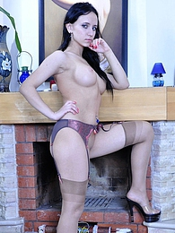Hot raven-head teasingly rides up her skirt flashing the tops of her nylons pictures at find-best-lingerie.com