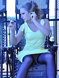 Black-stockinged exhibitionist smokes a cig and strips naked on the balcony pictures at find-best-panties.com