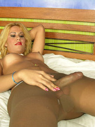 Smashing shemale squeezing her tits before spraying cum on her tan tights pictures