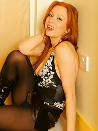 Sexy redhead Alexandra in opaque tights and leather mini pictures at kilomatures.com