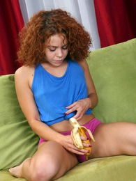 Very cute and curly redhead loves playing with a banana pictures