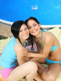 Horny bikini lesbians caressing cooters near a big pool pictures at kilosex.com
