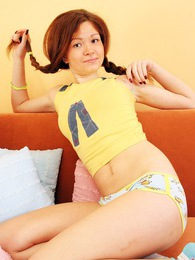 A teenage brunette undressing and fondling on the couch pictures at adspics.com