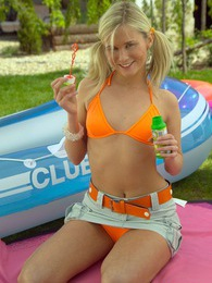 Cute teenage chick blowing bubbles in a boat in the garden pictures at lingerie-mania.com