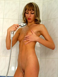 Sweetie playing with a showerhead on her very damp clit pictures at freekilosex.com