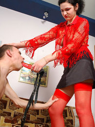 Red-stockinged babe with mighty strap-on is about to drill guy's banghole pictures
