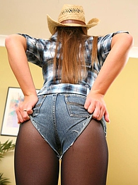 Sexy cowgirl in a tight checked shirt and tiny ripped denim hotpants pictures