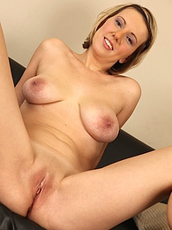 Blond MILF Luci Angel masturbating on the black sofa pictures at kilogirls.com
