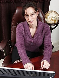 Mature office babe Shelly Jones naked on her desk pictures at lingerie-mania.com