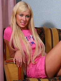 Sexy young blonde reveals her sweet shaved pussy on the couch pictures at freekilosex.com