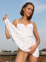 Attractive gal plays with her neat white dress while posing outdoors. pictures at find-best-panties.com