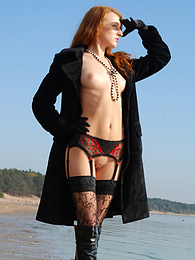 Sexy redhead girl spreads legs while posing in black coat and boots. pics